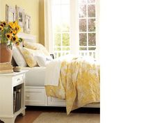 This bedroom stays on the sunny side with a vibrant wall shade that's carried into the antique-inspired bedding. A white-finished platform bed softens the bright look – and adds substantial storage with its spacious paneled drawers. Rustic mirrors modeled after Victorian tiles bring a weathered element into the light, airy space.  Benjamin Moore™ Paint Color: Squish-Squash; 311