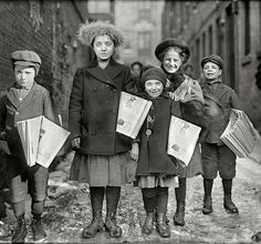 CITY LIFE, YOUTH: March 1909. Hartford, Conn. Newsgirls coming through the alley. The little person on the right looks like a boy and in charge of the crew. Also, they seem to be related.