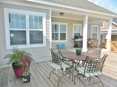 Covered patio & wooden deck extends out to the backyard in this lovely Tallahassee home.