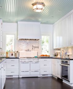 bead board on the ceiling, windows on either side of the stove, water over stove, white cabinets with black countertops