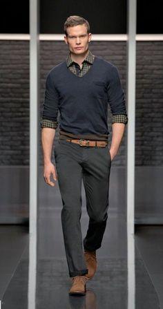 grey pants, a black sweater over a plaid shirt