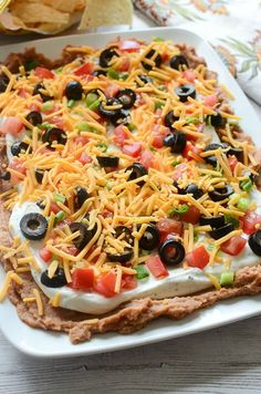 Layered Ranch Taco Dip - layers of refried beans, sour cream with ranch, tomato, olives, cheese, and more! No cooking involved!
