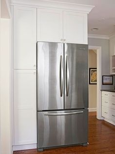 Surround a freestanding refrigerator with wood walls and a deep upper cabinet. Check fridge ventilation needs first./