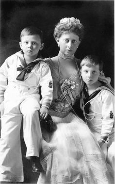 Princess Margaret of Hesse, nee Prussia, with two of her sons, wearing a diamond tiara, featuring five round floral motifs, interlinked by diamond pinnacles and horizontal bands.