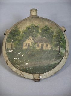 Civil War metal canteen featuring oil paintings of the Dunker Church on one side, and the Burnside Bridge on the other. This canteen was donated by Elmer Boyer, a local man, who salvaged the wreckage of the Dunker Church when it collapsed in a windstorm in 1924, and preserved the materials until 1962 when it was reconstructed. (Antietam National Battlefield)