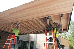 David Terry, left, and Kevin Scerini, both carpenters with Carpentry Plus, Inc., work on the soffit above the building's main entry.