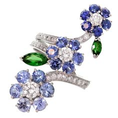 This magnificent 3-flower ring from Van Cleef & Arpel's Folie des Pres collection is made in 18k white gold and features 17 blue sapphire petals in different shades of an estimated 2.70 carats, 2 vivid green tsavorite leaves of an estimated 0.65 carats, accented with sparkling brilliant-cut round diamonds.This delicately asymmetrical collection is inspired by the colorful forms of wildflowers. c. 2000s