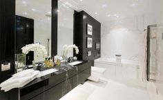 london bathroom design in black and white, supplemented by gloss black vanity unit, large mirror, a soking tub and a white toilet