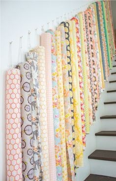 Roll up bolts of fabric and hang on wall