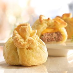Petite burgers get jazzed up with melted cheese and puff pastry to create an appetizer everyone will adore.