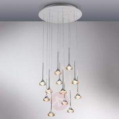 Mehrflammige LED-Hängeleuchte Fairy Die LED-Hängeleuchte Fairy entspricht zunächst nicht der klassischen Hängeleuchte, viel eher ähnelt sie einer Pendelleuchte. Denn eine Deckenhalterung oder ein einheitlicher, umfassender Leuchtschirm sind nicht Teil des im Vordergrund stehenden Ensembles. Insgesamt zwölf Flammen gehen an einer verschiedentlich ausstaffierten Abhängung in Richtung Boden. Die kleinen Leuchten mit jeweils 6,6 Watt Leistung wirken wie Tropfen, die relativ breit ausfallen. Ihr…