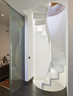 Interbau inserisce in un vano semicircolare una scala a chiocciola realizzata interamente in legno laccato bianco.