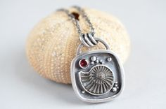 Sterling silver, ammonite and garnet pendant by laurenmeredith