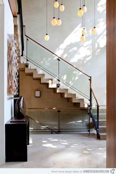 A modern minimalist concrete floating staircase combined with glass railings and wood banisters.