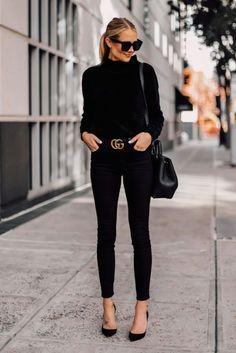 Chica por la calle luciendo un outfit negro en tacones y cinturón dorado