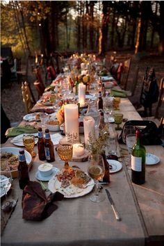 long forest table, mismatched dinner ware, candles, bottles, low light... perfect.