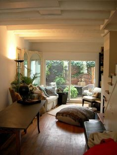 """Tiny rowhouse on Pomander Walk in Washington DC. Just 580 sq.ft. (11 ft. wide), w/two bedrooms. """"We were especially charmed by her use of the garden as an extension of the house."""" """"[The homeowner] knocked down the back wall and put in glass doors, giving her a bright space where she can to pursue her painting and enjoy a secret garden in the heart of Georgetown."""""""