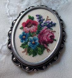 Pretty vintage petit point brooch featuring a roses and other flowers in pink, blue purple and lavender with green leaves. Needlework is set in