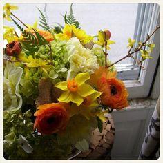 Spring mix of forsythia, orange ranunculus, daffodils, hydrangea and burlap ribbon.  Roberts Flowers of Hanover, Hanover, NH