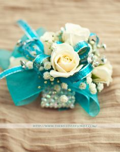 The Elsa,  A fantastic, sparkly corsage! White roses with a touch of babies breath in turquoise sparkle ribbon and aqua sheer ribbon. Large rhinestones compliment this piece. It comes with an iridescent, shimmery bracelet to add just the right amount of icy fun to this wrist corsage! — at Bellevue Florist.
