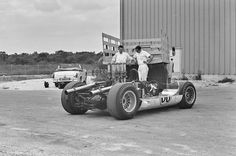 At Nassau, 1965, the Chaparral 2C sits stripped of its bodywork. Based on the tub of Chevy's GSIIb, the 2C was Chaparral's first car built on an aluminum tub. The car would be involved in a crash during the race. Taken back to Midland, it would be repaired and built into the revolutionary 2E. Leaning on the truck is Karl Schmid (on left) and another crew member I can't identify. Off to the left is an Austin Healey Sprite Mk.III (roll-down side windows). Eric della Faille photo.