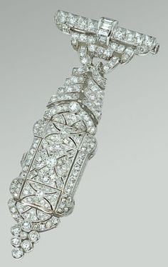 An Art Deco diamond lapel watch, circa 1925. The bar surmount of circular and baguette diamonds suspending a stylised articulated foliate garland of additional circular-cut stones, the watch concealed by an open work floral motif millegrain-set with circular- and single-cut stones, to the engraved scroll gallery, partly legible French assay and maker's marks. #ArtDeco #LapelWatch