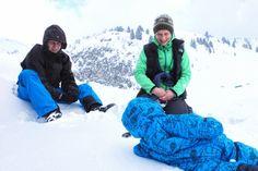Selbstversorgerhütte in der Schweiz. Tina un Daniel wälzen sich mit ihrem Baby im Neuschnee auf dem Berg.
