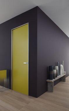 Un mur sombre et des portes peintes dans des couleurs vives, avec une baguette aluminium sur le cadre pour une finition épurée  design #dentist