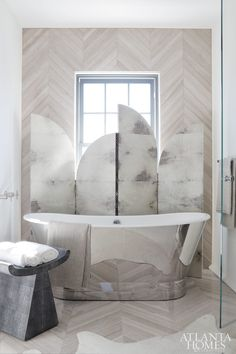 mirrored tub, marble look partition, hard wood floor