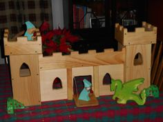 Our Finished Castle for our daughter this Christmas! Complete with a drawstring bridge! Made with about $25 worth of pine, we dremeled the edges with a sanding drum. we added the rose bushes on the side to keep it from tipping forward when she played. Finished with beeswax and orange oil, Rose bushes painted with acrylic folk art paint.  We are happy with our first attempt at a Waldorf inspired Wood Castle!