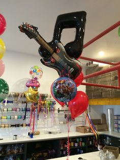 """I like to describe this bouquet theme as """"Musical Avenger-iness"""" with giant double quaver music note, flame guitar and Avengers Assemble 18"""" foil and lots of red latex balloons"""