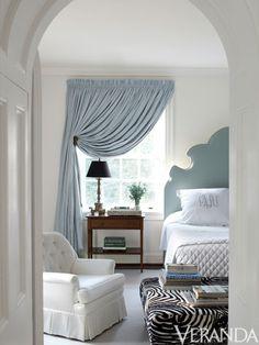 An elegant monogram adorns crisp white bedding in this bedroom by Suellen Gregory (Veranda, July/August 2012).