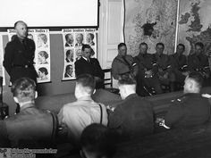 Lessons in Racial Politics at a Hitler Youth Leadership School (c. 1935): This photograph shows Helmut Stellrecht (left), regional leader of the Hitler Youth, giving a lecture on racial politics at a Hitler Youth Leadership School. Alfred Rosenberg is seated closest to him. Rosenberg partially obscures one of two posters featuring positive examples of members of the German race. Photo by Heinrich Hoffmann.