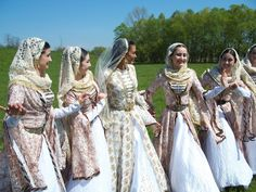 A group of young women sporting beautiful, pale hued traditional Chechen folk costumes