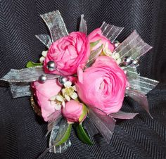 All Seasons Floral- Wrist corsage with pink ranunculus and silver accents.