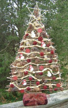 Plain and simple Christmas tree shaped hanging decoration made of woven  natural willow with a wooden star button and a raffia loop which can.