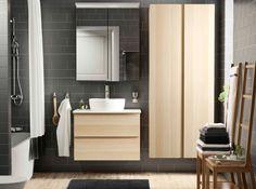 Badeværelse med gråbrune fliser, et skab til vask med egetræsmønster og hvid bejdse samt et højskab. Kombineret med en hvid vask og et vægskab med spejllåger.