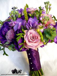 "Bride's bouquet of purple lisianthus, purple stock, purple delphinium, purple freesia, dusky purple and coffee ""old dutch"" roses, with touches of ladder fern, eucalyptus and berries, bound in deep purple satin.    Visit us here:  www.blossomweddingflowe"