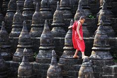 A young monk steps gingerly across stupas that forms part of a Buddhist temple in Mrauk-U, Rakhine, Burma. By Alika