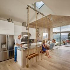 The swings-as-barstools idea in this modern kitchen came from the family's travels – they saw similar swings in a bar and never forgot them. The kitchen was designed to be a fun space for the parents, their kids and their friends. Since they often entertain, the goal was to make the kitchen and living room one open, flexible space with an airy feel and a strong connection to the outdoor view.