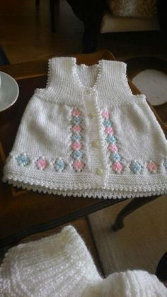 Knitted baby vest. Flowers embroidered on lace pattern