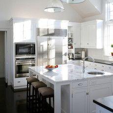 ホワイトが基調の広々としたキッチンスペースは、カウンタートップの大理石とスツールのブラウンが映えて機能的で美しいイメージ。部分的に使われたシルバーがクリーンな印象。