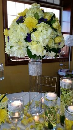 Arrangement of yellow tinted hydrangea, purple statice, yellow spider mums and yellow roses atop a clear glass cylinder with a large diamond band.  DorisTheFloristt.com