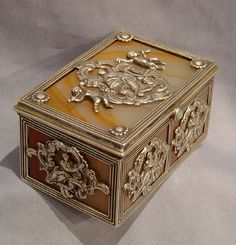 A very fine ly worked and attractive silver and splitagate box. Beautifully made and fully lined the matched agate veneers are backed with silver. The lid has silver mount in the rococco style of a classical woman within the clouds and gambolling Cupids either side. The front and sides of the box are decorated with silver mounts of a classical woman. Dutch circa 1880...........Gavin Douglas Antiques