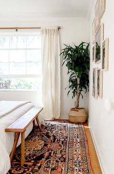 Skinny wood bench at the end of bed, multicolored bohemian rug, plant in rattan basket, gallery wall