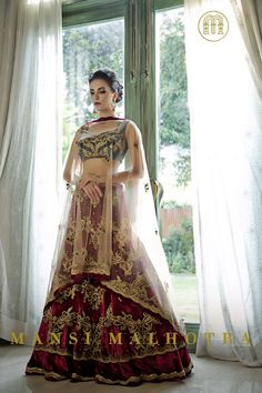 Velvet Maroon Bridal Lehenga >> Velvet maroon bridal lehenga with emerald green crop top and a beige net dupatta in gold zari with crystal, bead, and sequin embroidery.