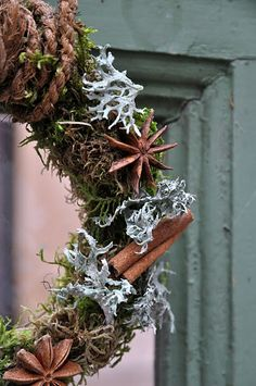 birch twig wreath decorated with moss, lichen, star anise, cinnamon bark, hung with coir twine