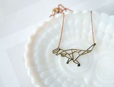 A lightweight yet sturdy brass charm in the laser cut shape of a T-rex in modern geometric lines. Hung on a vintage raw brass 16 inch chain, this necklace is perfect for the dino lover in your life. Wear it alone, or layer it up for a statement.  Comes gift boxed and ready to give.   looking for ot