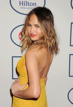 Chrissy Teigen showed off a honey-hued lob orange lipstick at the 56th Annual Pre-Grammys Gala..