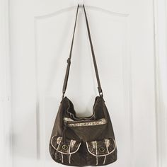 """Maurice's Floral Trim Cross Body Maruices Cross Body  ·         Brown ·         Faux leather ·         Magnetic snap closure ·         Adjustable shoulder strap ·         Floral cotton trim detail ·         3 pockets on front ·         2 interior slip pockets ·         Interior zipper pocket ·         *one of the pockets on front is broken (see pic) ·         Measures 11.5x4x12 ·         Strap 22.5"""" Maurices Bags Crossbody Bags"""